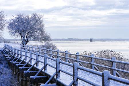 snowy wooden footbridge walking trail on the lakeshore in winter Stock fotó