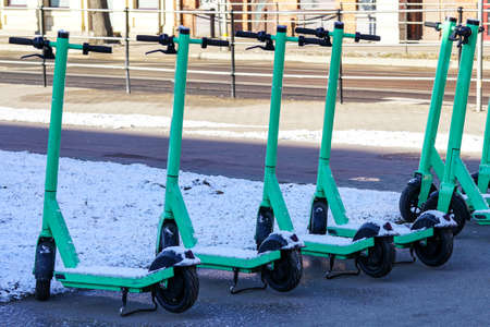snow covered rental electric scooters on a city street in winter