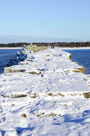 winter seascape, port entrance with snow covered concrete blocks breakwater 版權商用圖片
