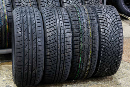 four new tires with different treads for summer, all season, winter with soft rubber and winter with studs