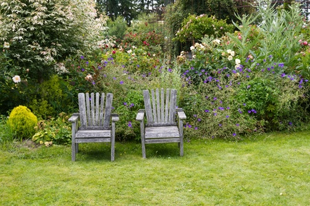 A pair of wooden chairs in the garden Banco de Imagens