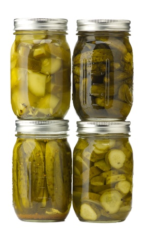 Four jars of assorted homemade pickles isolated