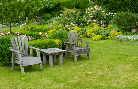 A pair of chairs and small table in the garden Banco de Imagens