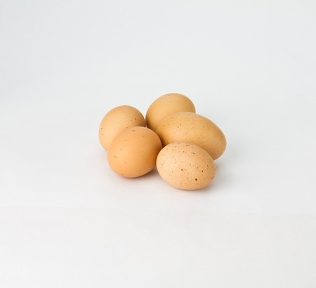 Five fresh speckled brown eggs on white
