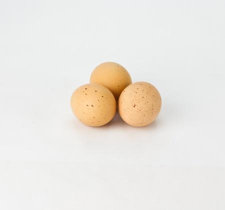Three fresh free range speckled brown eggs on white Banco de Imagens