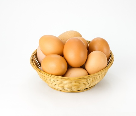Fresh brown eggs in wicker basket on white