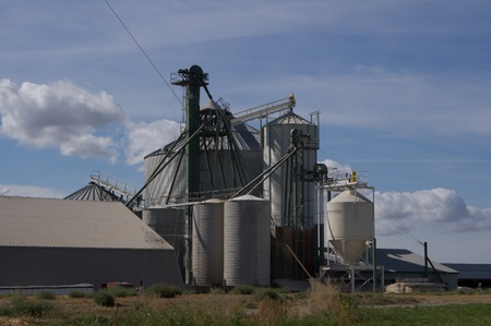 grainery: Grain storage silos and milling facility with bright clouds in sky Stock Photo