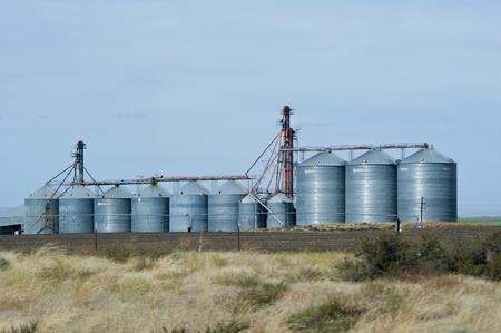 grainery: Steel grain silos and elevators with harvested field Stock Photo