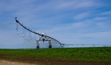 A large pivot irrigation system supplies water to cropland by traveling and spraying water