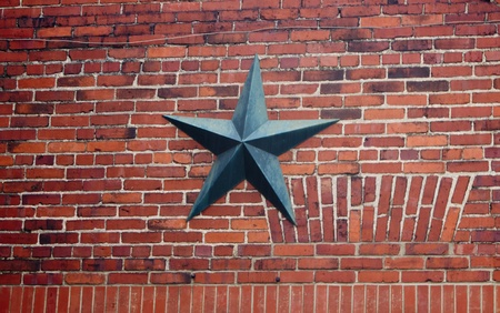 A brick wall reinforced with a cast iron star washer and bolt