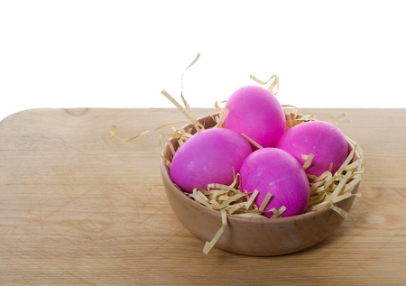 A small wooden bowl filled with colorful eggs sitting on a table photo