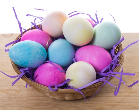 A wicker basket of colorful dyed Easter eggs and purple straw sitting on a table photo