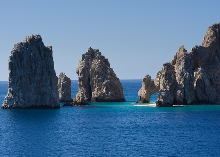 Rock formations including El Arco rise from the sea