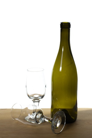 A wine bottle on a table with two glasses photo