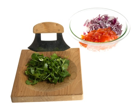 A chopping board and knife with ingredients diced to make salsa photo