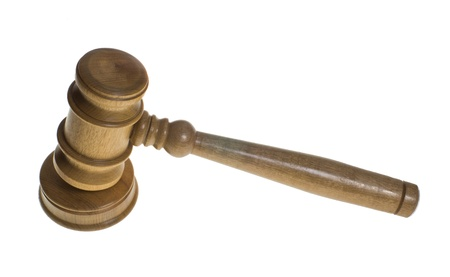 A wooden gavel rests on a striker isolated on white