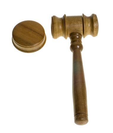 A wooden gavel rests beside a striker plate isolated on white Stock Photo
