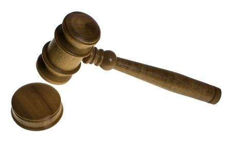 A wooden gavel is about to hit the strike plate isolated on white