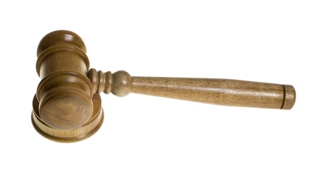 A wooden gavel rests on top of the strike plate isolated on white