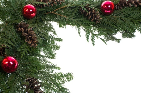 A decorative border of pine boughs ornaments cones isolated on white Stock Photo - 12305532