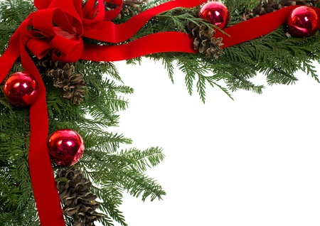 religious event: A decorative border of pine boughs ornaments cones ribbon and bow isolated on white Stock Photo