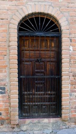 An old wooden door with details set in brick