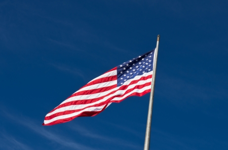 An American flag flutters in the breeze under a blue sky