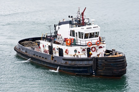 A tug boat stands ready to help ships in the Panama Canal Stock Photo