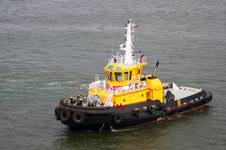 A bright yellow tug boat standing by to help ships in the harbor photo