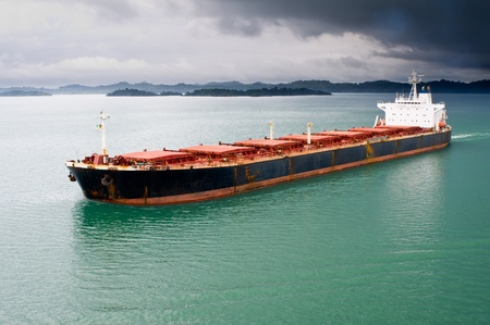 A bulk freighter travels through the Panama Canal under stormy skies