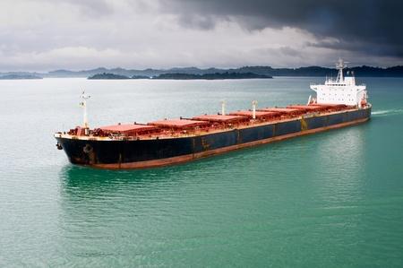 Un cargo en vrac se d�place � travers le canal de Panama sous un ciel orageux Banque d'images