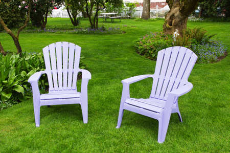 Two chairs on a green lawn in the garden photo