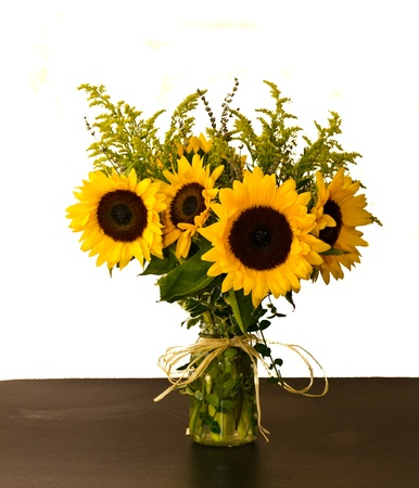 A colorful arrangement of sunflowers and goldenrod in a glass vase