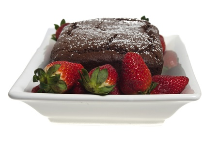 A chocolate cake on a white plate with ripe strawberries