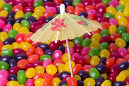 An umbrella on a beach of jelly beans Stock Photo