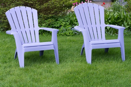 Two purple chairs sitting on a fresh green lawn photo