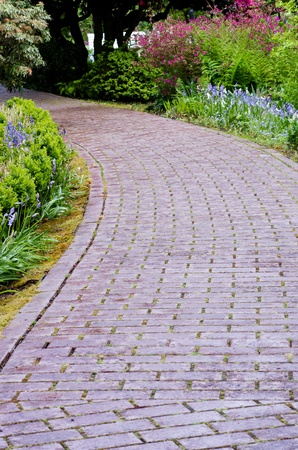 A winding garden path of red pavers with flowers photo