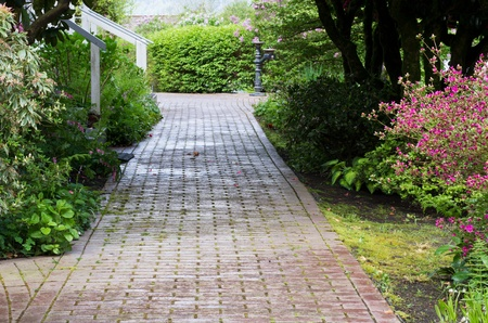 A garden path with flowers goes through a wooded area Stock Photo