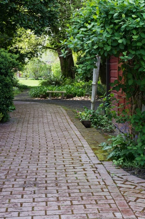A paved garden path with garden shed and trellis Фото со стока