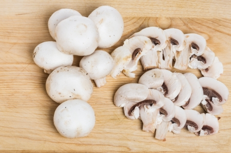 Seven white button mushrooms and slices on a cutting board Stock Photo - 13615571