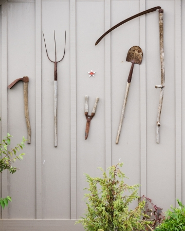 A group of tools hanging on the shed wall Stock Photo