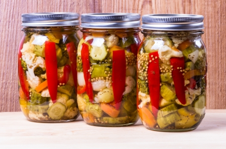 Three jars of homemade preserved hot mixed vegetables photo