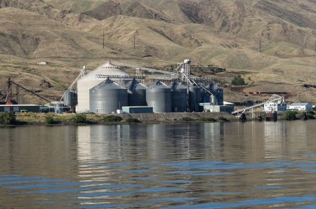 A metal grain silo storage facility on a river photo