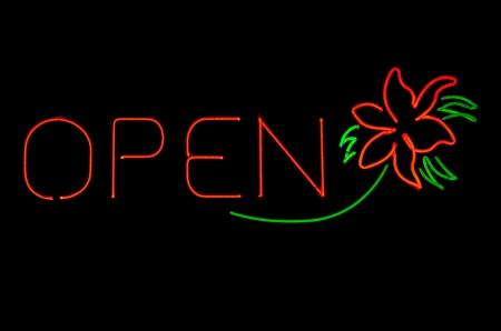 Een heldere neon open teken met bloem Stockfoto
