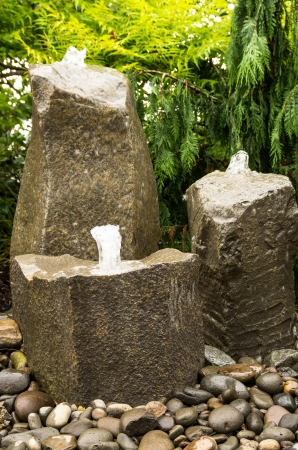 fontana: Tre fontane acqua che sgorga roccia in un giardino