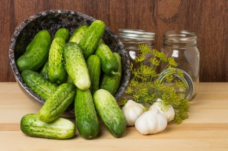 Bowl full of fresh pickles with jars dill and garlic to make pickles photo