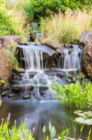 A flowing waterfall with grass and flowers in the park Stok Fotoğraf