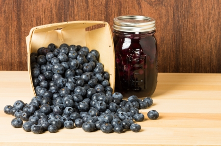 Blueberries spilling from wooden container with jar of fresh blueberry jam Banco de Imagens