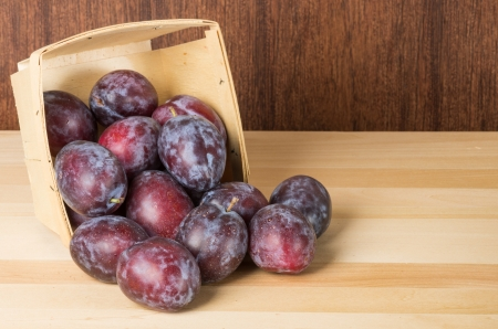 prune: Prune plums spilling from wooden container onto table