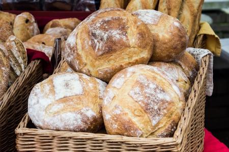 canasta de panes: Panes frescos horneados de pan en cesta de mimbre